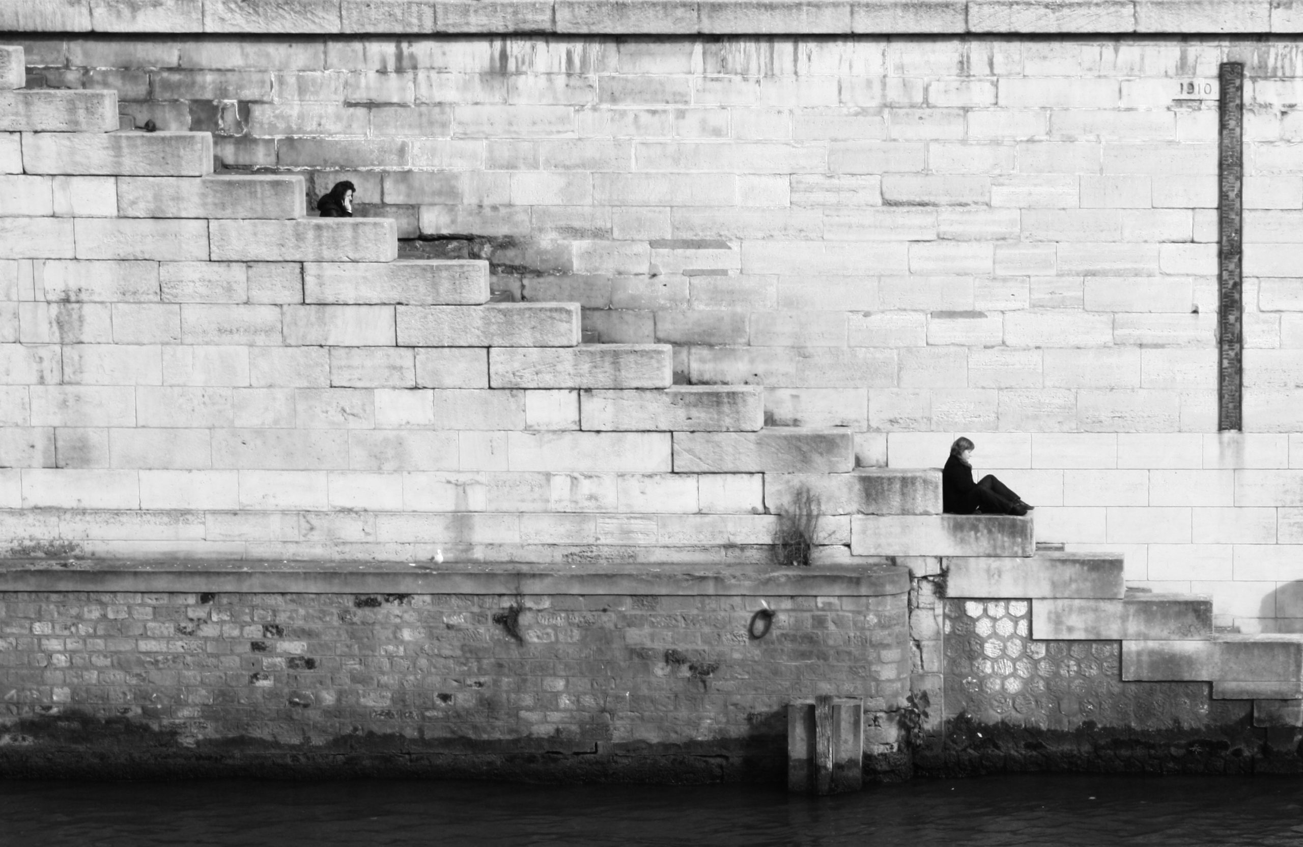 Landscape photograph of a woman sitting alone by a wall